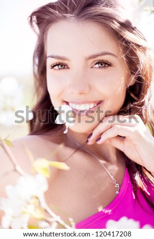 beautiful young brunette woman with a flower in her teeth standing near the apple tree on a warm summer day