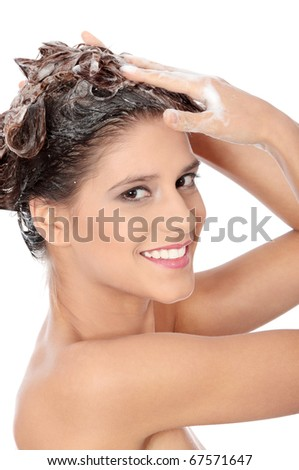 Beautiful young brunette woman with attractive smile soaping her head - isolated on white background