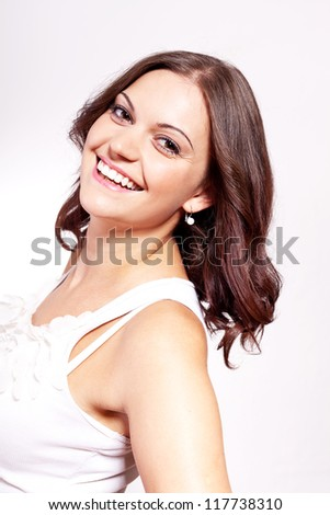 beautiful young brunette woman with big smile on white