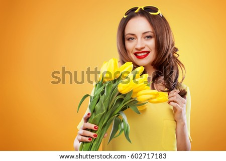 Beautiful young brunette woman with yellow tulips on yellow background #602717183
