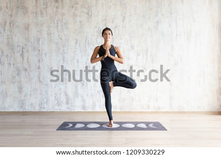 Beautiful young brunette woman yoga instructor doing vrikshasana on a mat in a wooden floor standing in the gym with day lighting