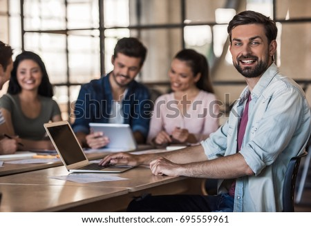 Beautiful young business people in casual clothes are using gadgets and smiling while working in office #695559961