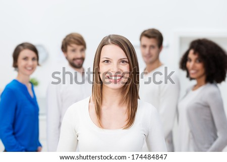 Beautiful young business team leader standing in front of her successful team smiling broadly at the camera confident in their success