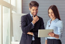 Beautiful young business woman and handsome businessman in formal suits are using a digital tablet, talking and smiling while working in office