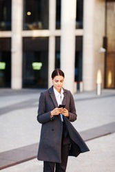 Beautiful young business woman in coat text messaging on cell phone while walking down city street on windy day