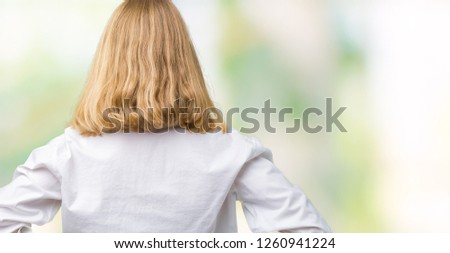 Beautiful young business woman over isolated background standing backwards looking away with arms on body
