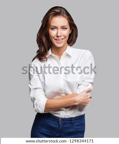 Beautiful young business woman portrait. Smiling successful girl looking at camera isolated on gray background. Studio shot of  good-looking happy female with crossed arms dressed white shirt