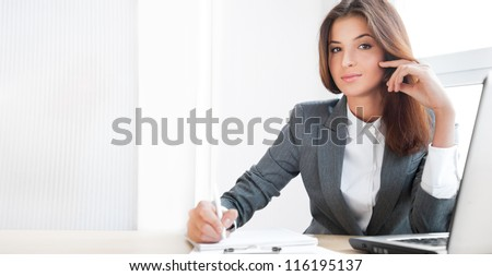Beautiful young business woman sitting relaxed at her office and looking at camera