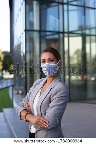 Beautiful young business woman standing with crossed arms and wearing facial protective mask in front of glass building. Pandemic protection and responsibility in business Stock photo ©