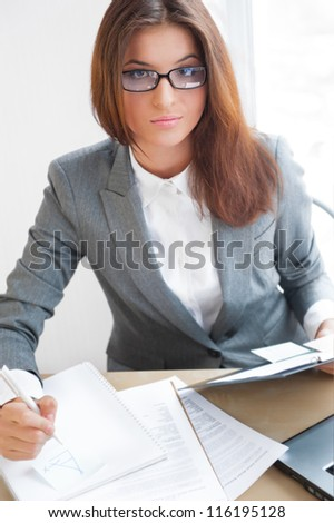 Beautiful young business woman wearing glasses sitting relaxed at her office and looking at camera