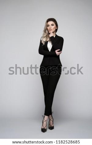 Beautiful young business women wearing jacket and high heels. Business women wearing jacket posing in photo studio. Photo studio portrait. Vertical. Grey background.