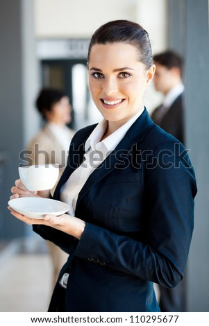 beautiful young businesswoman drinking coffee in office during break - stock photo