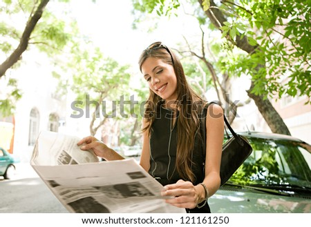 Beautiful young businesswoman reading a newspaper while leaning on a car in the financial district of a classic city street aligned with trees on a sunny day.
