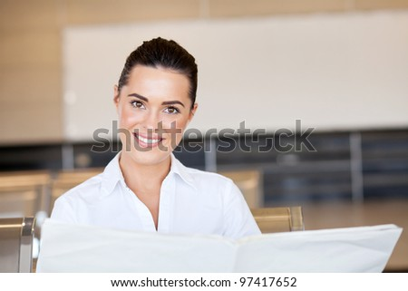 beautiful young businesswoman reading newspaper at airport