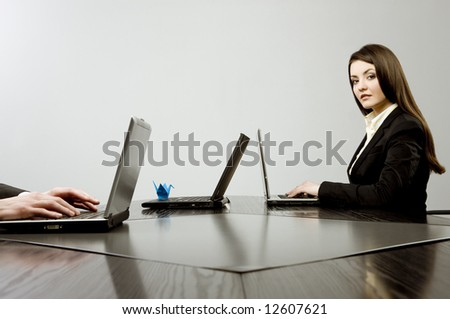 Beautiful young businesswoman sitting at a desk with three laptops with blue origami on one of them and human hands on another one