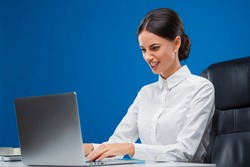 Beautiful, young businesswoman sitting at her desk fiercely typing her ideas, isolated on blue background.