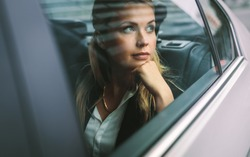 Beautiful young businesswoman sitting on back seat of a car and looking outside the window. Female business executive travelling by a cab.