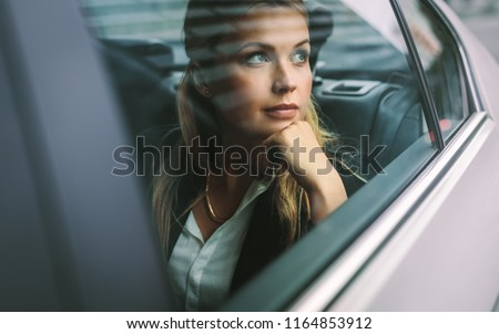 Beautiful young businesswoman sitting on back seat of a car and looking outside the window. Female business executive travelling by a cab. - Shutterstock ID 1164853912