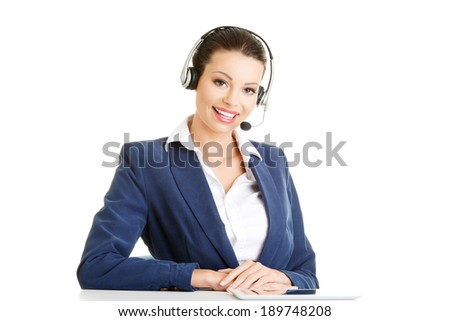 Beautiful young call-center assistant at the desk, isolated on white