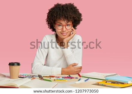 Beautiful young cartoonist or animator wears eyewear, white casual sweater involved in creative working process, makes sketches in blank notebook, has coffee break, isolated over pink background