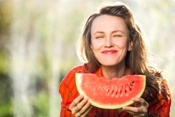 Beautiful young caucasian brunette woman  holding a watermelon slice. Healthy food and happy summer holiday concept