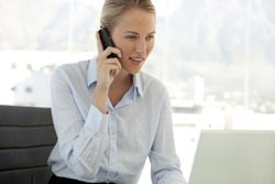 Beautiful young caucasian businesswoman on the phone looking at computer at workplace
