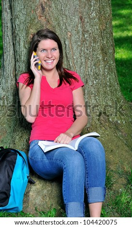 Beautiful young Caucasian female student sitting under a tree talking on a cellular phone while studying or reading