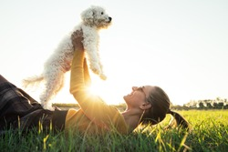 Beautiful young caucasian girl playing with her dog lying on the grass in the park at sunset. Animal, friendship, people and love concept