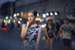 Beautiful young caucasian girl under the lights of the night city, bokeh, light lamps and vehicles