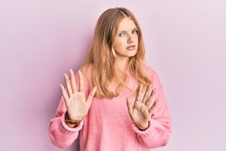 Beautiful young caucasian girl wearing casual clothes moving away hands palms showing refusal and denial with afraid and disgusting expression. stop and forbidden.
