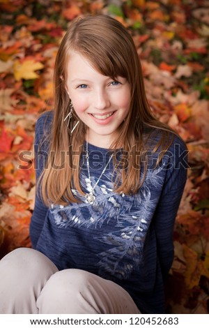 Beautiful young Caucasian girl with blonde hair and blue eyes sitting in a pile of fallen leaves