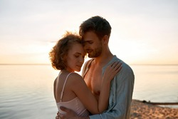 Beautiful young caucasian lovers hugging each other while dating on beach at sunset. Romantic date concept