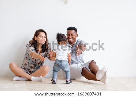 Beautiful young Caucasian woman couple and an African American man are pulling their hands to their charming mixed race daughter. Concept of posing on white background. Copyspace Foto d'archivio ©