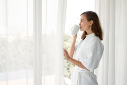 Beautiful Young Caucasian woman in pajamas holding a glass of white coffee ready to drink by the window in the bedroom at home after wake up in the morning. Woman standing drinking coffee by window.