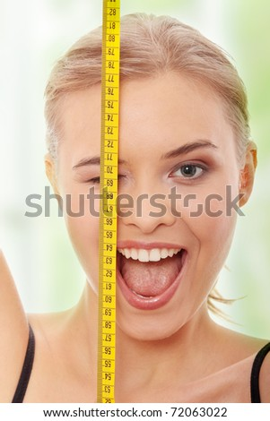 Beautiful young caucasian woman measuring her body with tape