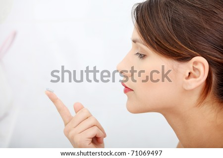 Beautiful young caucasian woman putting a contact lens at bathroom