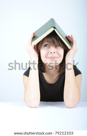 Beautiful young caucasian woman with book on her head, looking up