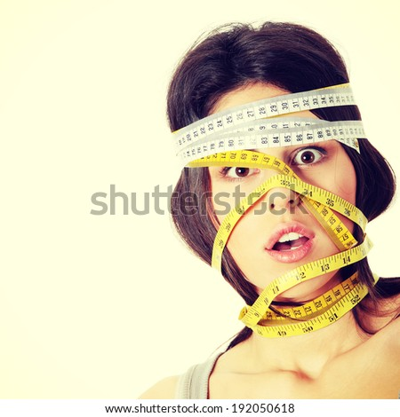 Beautiful young caucasian woman with measuring tape around her head. Diet concept