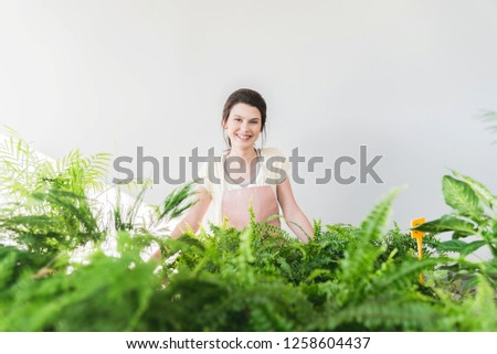 Beautiful young cheerful plants enthusiast working and learning in botanical garden, Ecology praxis concept,Space for text on a white background