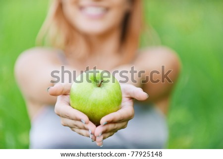 Beautiful young cheerful woman with green big apple, against green summer garden.