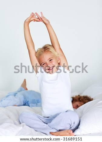 Beautiful young child stretching after sleeping