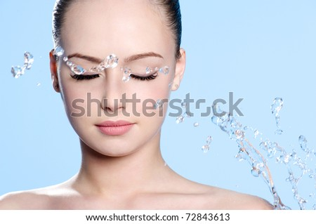 Beautiful young clean female face with splash of water - blue background