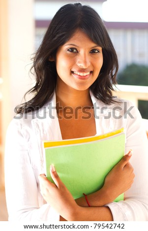 beautiful young college student in school building with books