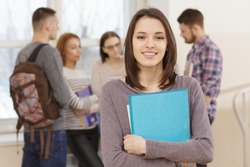 Beautiful young college student standing in front of her friends in the hallway smiling to the camera holding her books copyspace education togetherness relationships friendship study campus concept