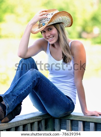 Beautiful young country and western girl in white tank top, blue jeans and a western or cowboy hat