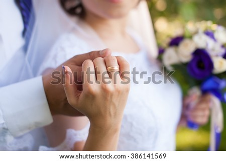Beautiful young couple a man and a woman. Close-up hand of groom and bride with a wedding ring. Focus on the arm and the ring. bride in white dress. The picture is cropped without faces. #386141569