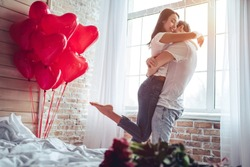 Beautiful young couple at home. Hugging, kissing and enjoying spending time together while celebrating Saint Valentine's Day with red roses on bed and air balloons in shape of heart on the background.