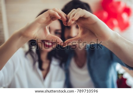 Beautiful young couple at home is making heart sign with hands, smiling and looking at camera. Celebrating Saint Valentine's Day.