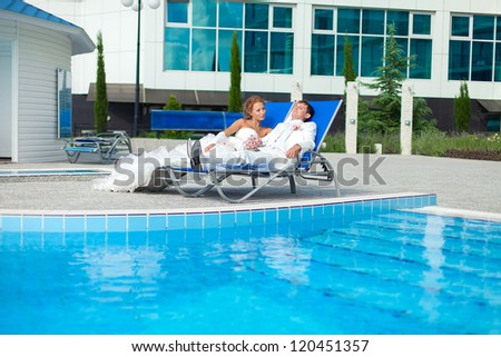 Beautiful young couple bride and groom posing on deck chair on a background a luxurious hotel and swimming pool in their wedding day in summer. Series.