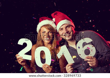 Beautiful, young couple celebrating New Year\'s Eve, holding cardboard numbers 2016
